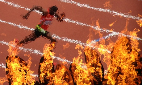 Sudan's Rabah Yousif is captured through the Olympic flames as he competes in the Men's 400m heats