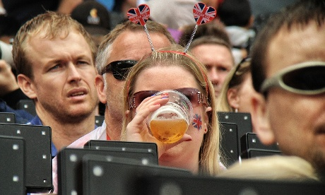 A British fan enjoys some refreshment whilst watching the morning's athletics in the Olympic stadium