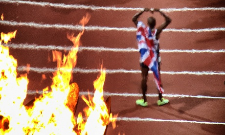 Mo Farah is seen through the Olympic flames as he poses with the Union Jack after winning gold in the Men's 10,000m final.