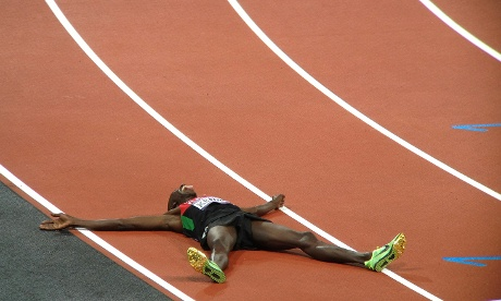 Kenya's Ezekiel Kemboi sticks out his tongue as he lies on the ground celebrating winning the gold medal in the steeplechase