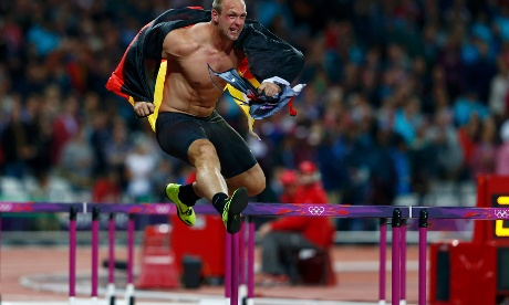 Germany's Robert Harting jumps over a hurdle as he celebrates winning the men's discus throw final during the London 2012 Olympic Games at the Olympic Stadium August 7, 2012