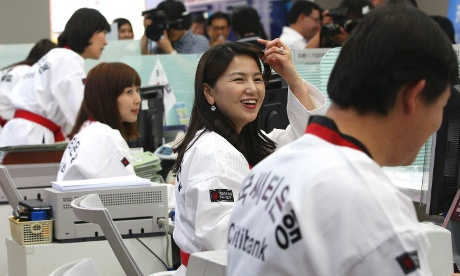 Employees clad in Taekwondo uniform working at a Citibank branch in Seoul, South Korea, this morning. They wore the uniforms to show their support for South Koreans competing in Taekwodo at the London Olympics. Photograph: Ahn Young-Joon/AP