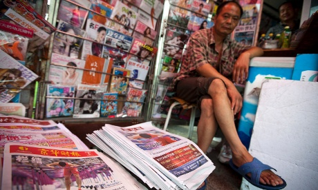 Local reaction: a vendor waits at a newsstand, where Chinese hurdler Liu Xiang's photos are seen on the local papers' front pages, in central Beijing this morning. Photograph: Alexander F. Yuan/AP