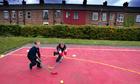 Primary school pupils playing hockey in a Manchester playground