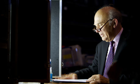 Vince Cable stands illuminated against darkness as he reviews a speech
