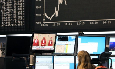 A trader watches a screen displaying the judges of the Second Senate of the Federal Constitutional Court (Bundesverfassungsgericht) as she works in front of a chart of Germany's share index Dax on September 12, 2012 at the German stock exchange in Frankfurt/M, western Germany.