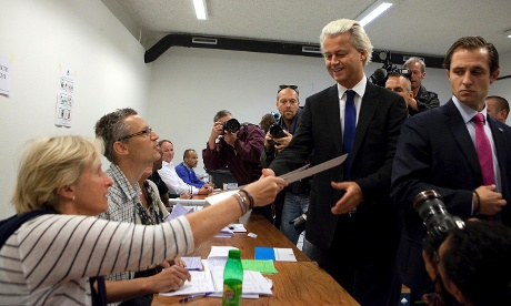 Freedom Party lawmaker Geert Wilders, second right, receives his ballot for parliamentary elections, with his bodyguard at right, at a polling station in The Hague, Netherlands, Wednesday Sept. 12, 2012.