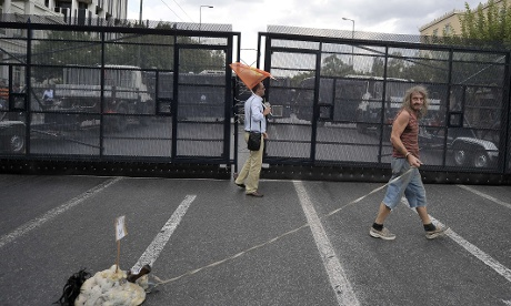 Protesters gather in front of the Greek parliament in Athens, protected by a fence on September 12, 2012.