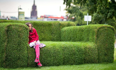 A woman sits on a grass-made sofa in Frankfurt, Germany. The so-called