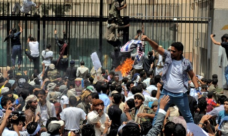 A Yemeni protester burns a US flag as others storm the US embassy in Sana'a during a protest against a film deemed insulting to the Prophet Mohammed.