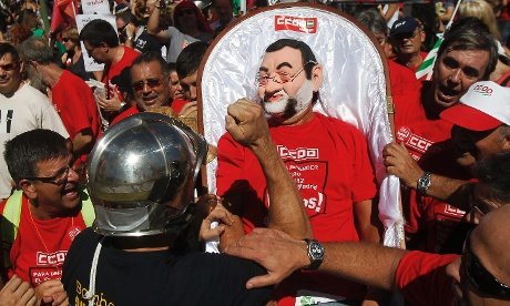 A fireman gestures towards a man dressed as Spanish prime minister Mariano Rajoy, centre, during protests in Columbus Square in Madrid on Saturday September 15, 2012.  Photograph: Andres Kudacki/AP