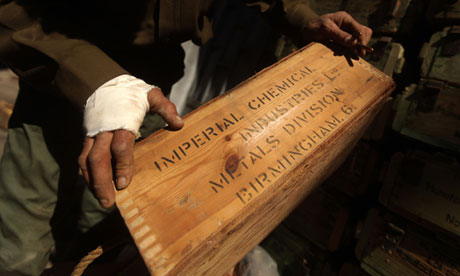 A Libyan rebel carries a box of British-made ammunition found at a military base in Benghazi