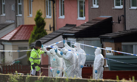 Police forensic officers outside a house in Hattersley where two police officers were shot