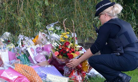 Police officer lays flowers close