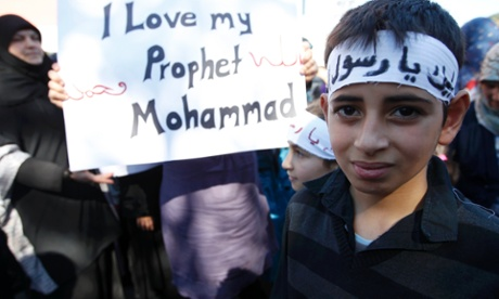 Muslim children hold up a placard before taking part in a protest march against a US made film and cartoons published by a French magazine in Freiburg.