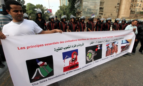 Egyptian protesters hold a banner during a protest over French cartoons mocking the prophet Muhammad, near the French embassy in Giza.