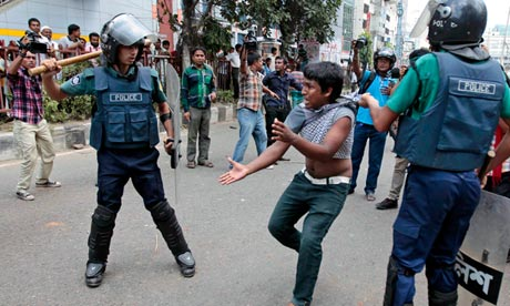 Bangladeshi policeman detain an activist from an Islamic group at a protest in Dhaka
