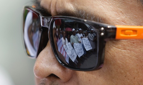Protesters are reflected on the sunglasses of a Filipino Muslim as they hold a protest rally near the US embassy in Manila this morning, 24 September.
