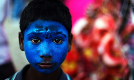 A boy with his face painted blue like the Hindu god Shiva,  stands near an idol of elephant headed god Ganesh near the  Ganges in Allahabad, India, at the weekend. Every year millions of devout Hindus immerse Ganesh idols into oceans and rivers during the Ganesh Chaturthi festival that celebrates the birth of the Hindu god.
