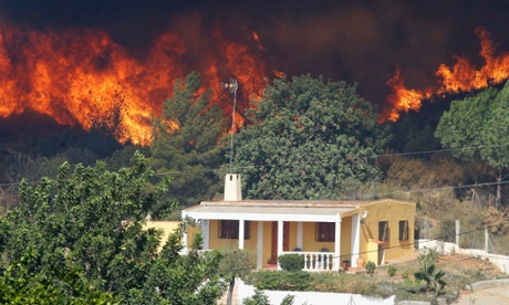Smoke from a wildfire engulfs a hillside next to a house in Pedralba near Valencia in Spain