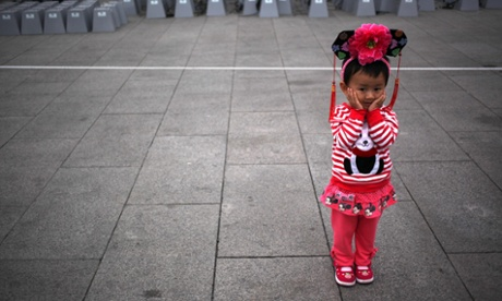 A Chinese girl wearing Qing dynasty headgear stands in Beijing's Tiananmen Square during preparations for National Day, which is on 1 October