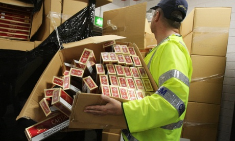 A customs officer with some of the more than 7.6m contraband cigarettes which have been seized at Dublin port. The haul of Capital and Master brand cigarettes has an estimated retail value of almost £2.4m