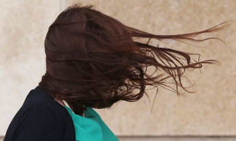 Bad hair day: A visitor to the seafront at Brighton feels the full force of the wind
