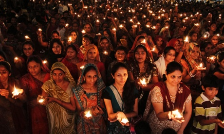 Hindu women and children hold earthen lamps as they take part in the Maha Aarti ritual on day five of the 10-day Ganesh Chaturthi festival in Ahmadabad, India