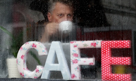 A man sips a drink in a coffee shop in Dublin as torrential rain and gale force winds sweep across Ireland as well as much of the UK.