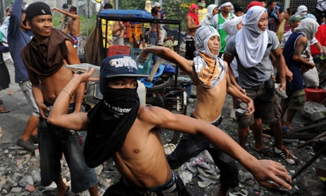 Residents throw stones and beer bottles at a demolition team and anti-riot police during an operation to clear a shanty town to make way for a government project in Manila.