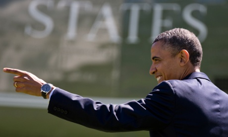 Barack Obama points to people on the south lawn of the White house in Washington, as he walks from the Oval Office to the presidential helicopter Marine One.
