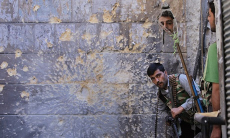 A Free Syrian Army soldier uses mirror to view Syrian Government troops around the corner, as he takes his position with his comrade during the clashes at the old city of Aleppo.  Photograph: Hussein Malla/AP