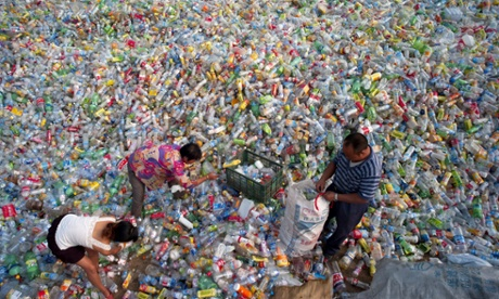 People sort plastic bottles for recycling at a reclamation depot in Qingdao, China. The waste recycling industry provides a livelihood to low income people living in temporary houses on the outskirts of Chinese cities.