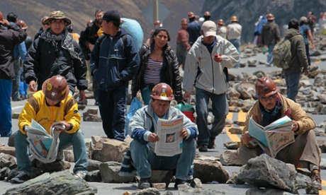 What page are we on? Bolivian independent miners read newspapers as they blockade a main highway in Pongo, on the outskirts of La Paz. Thousands of independent miners protested along a main highway surrounding La Paz city on Monday. According to local media, the miners were embroiled in a labour dispute with the unionized mine workers of Colquiri, the country's second-biggest tin mine, who accused them of violating an agreement between the two groups and wanted them barred from the site.  Photograph: David Mercado/Reuters