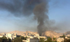 In Damascus, smoke rises from the site of twin explosions at a main military building
