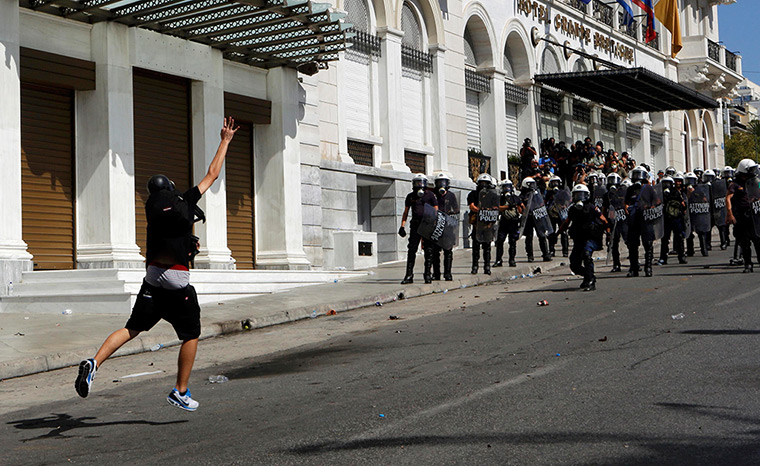 Greece protests update: A demontrator throws a molotov cocktail to riot police