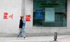 A woman walks past a Bankia bank branch in Madrid
