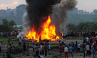 People gather near the burning plane after it crashed in Kathmandu, Nepal