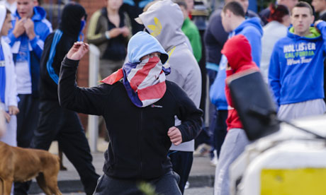 A youth with a union flag facemask throws stones at a police riot squad in Belfast
