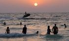 People enjoy a sunset swim at a public beach in Dubai, United Arab Emirates, this evening.