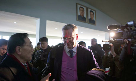 Eric Schmidt, the Google executive chairman, under portraits of Kim Il-sung and Kim Jong-il