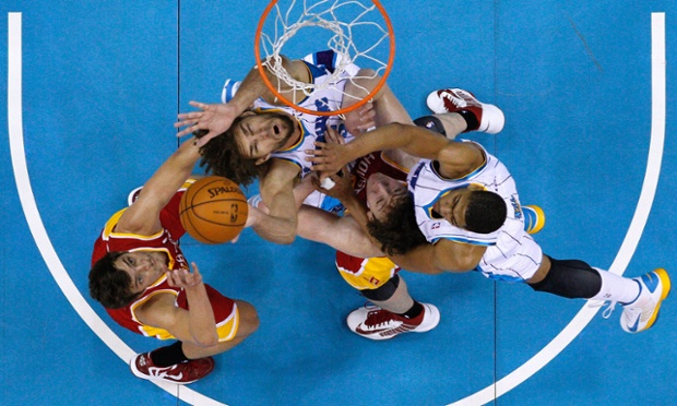 The photographer takes a birds-eye view to capture the tussle for the ball between Houston Rockets and New Orleans Hornets during the first half of an NBA basketball game in New Orleans.