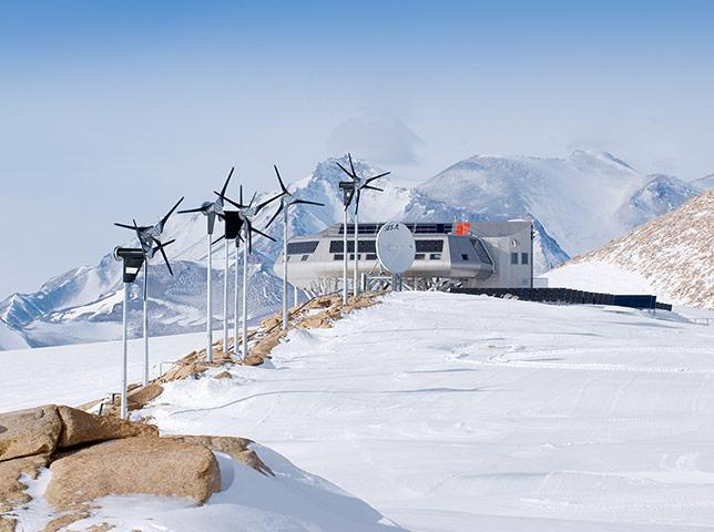 Penguins in Antarctica: Princess Elisabeth Station with windturbines, solar panels & satellite dish