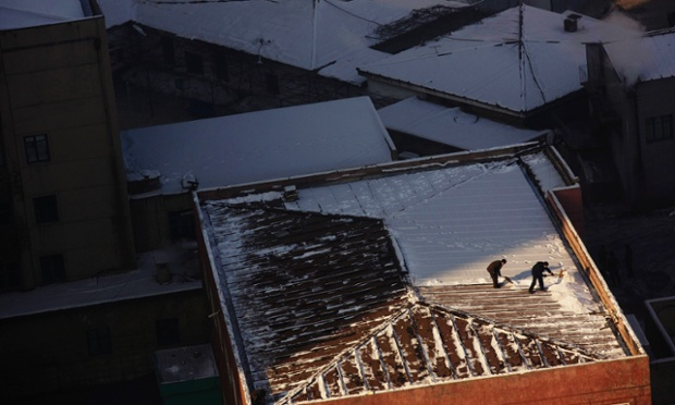 Up on the roof - North Korean men shovel snow from the top of a building in Pyongyang, North Korea.