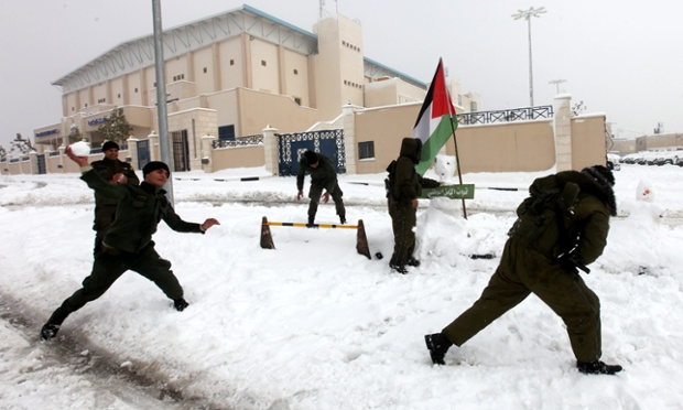 Palestinian security personnel engage in a snowball fight near their headquarters in the West Bank city of Hebron. The higher elevations in the Palestinian Authority areas and Israel, including Jerusalem, are expecting some 20 centimeters of snow overnight.