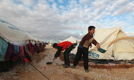 Syrian refugee children work to clear water collected outside their tents after heavy rain at the Za'atari refugee camp.
