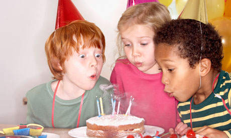 children blowing candles out