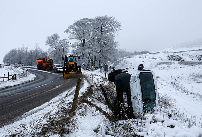Snow over UK: Snow ploughs drive past a van crashed  in Buxton