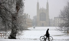 A man pushes a bicycle through the snow as he passes by King's College Chapel in Cambridge