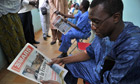 Mali man reads newspaper praising France